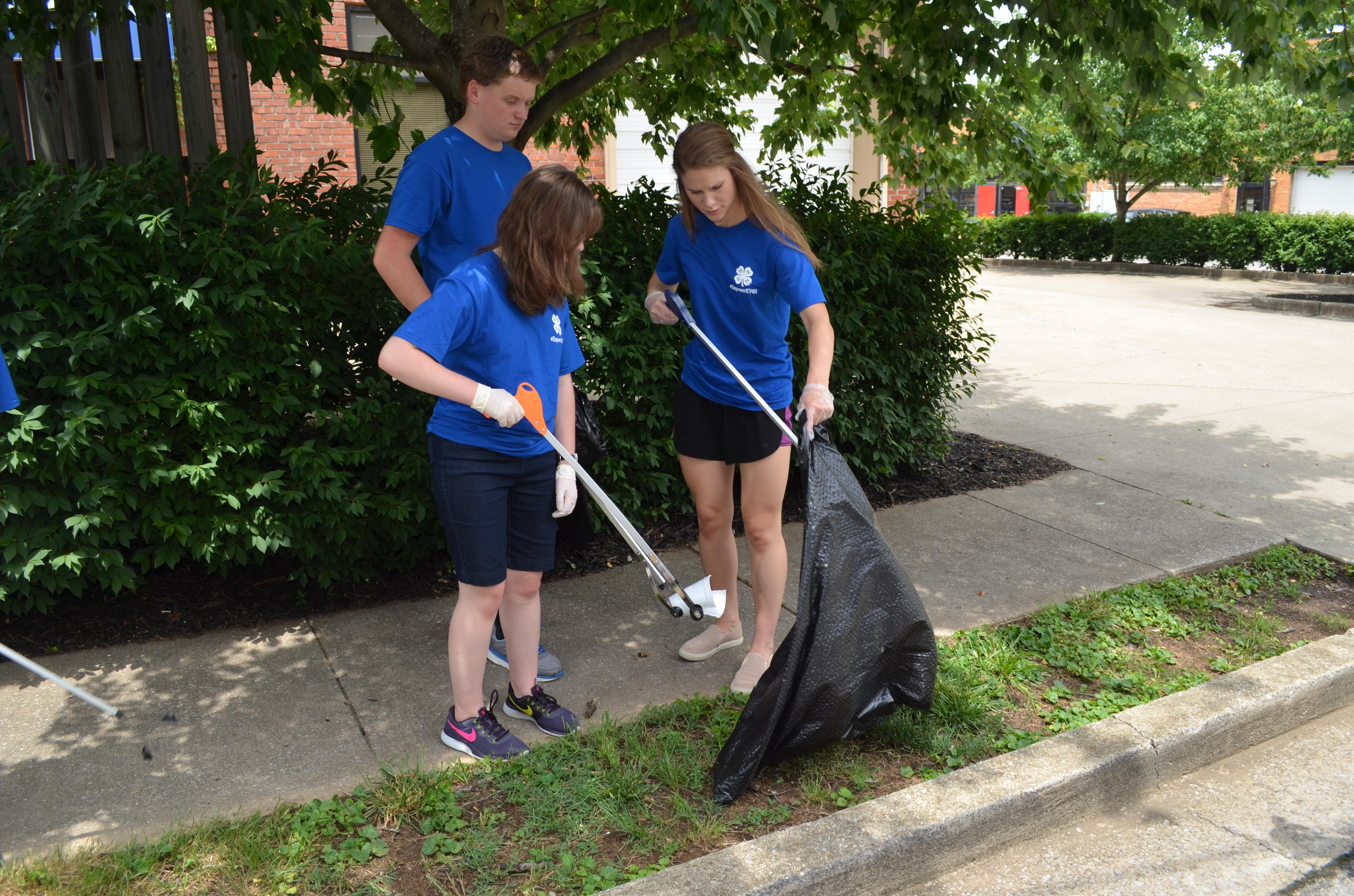 Kentucky 4-H'ers (l-r): Kayla Mohon, Raymond Carter, and Debbie Myers, pick up litter in a downtown Lexington neighborhood as part of their community service project with Bluegrass Greensource