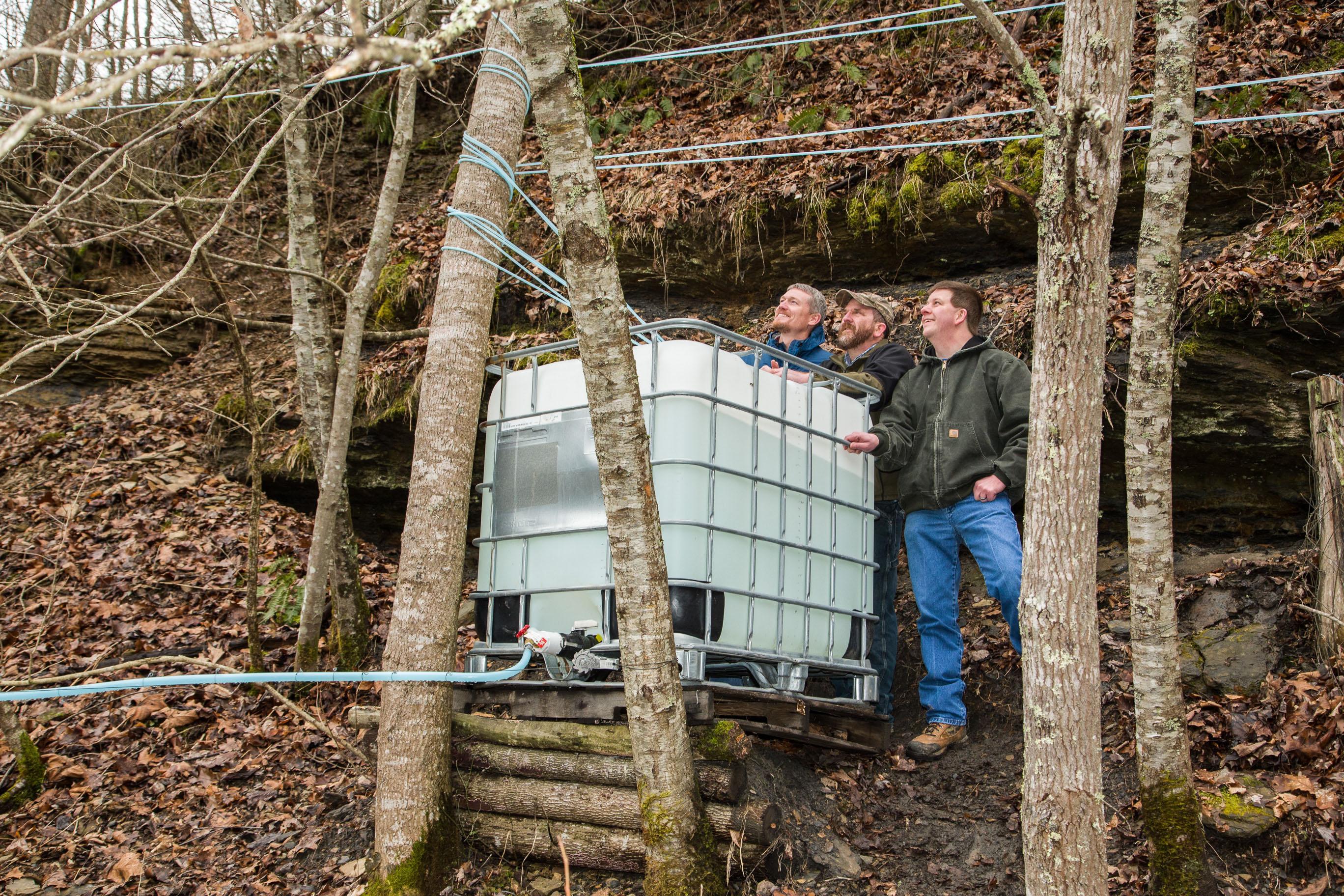 (L to R) Shad Baker, Seth Long, and Jeremy Williams discuss the season's collection. Here, a collection tank holds sap from multiple trees at Long's Southdown Farm in Letcher County. From the tank, the sap will run downhill to the sugarhouse, where the Lo